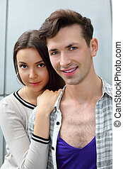 Beautiful smiling man and woman stand near gray wall; woman holds man shoulder; focus on man