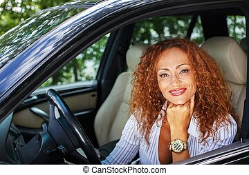 Beautiful smiling middle-aged redhead woman behind steering wheel