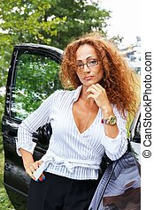 Beautiful smiling middle-aged redhead woman standing near car