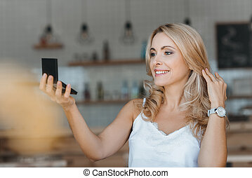 woman looking at cosmetic mirror - beautiful smiling middle ...