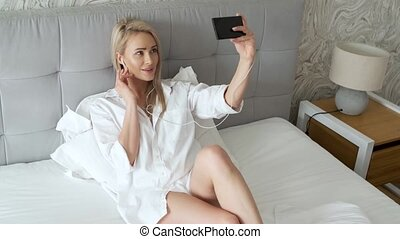 Beautiful, smiling middle aged woman making selfie in bedroom
