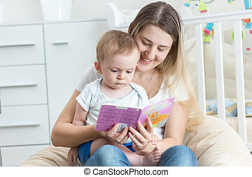 Beautiful smiling mother reading book to her 9 months old baby boy