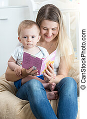 Beautiful smiling mother reading story to her 9 months old baby boy