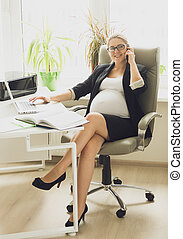 Beautiful smiling pregnant woman in black suit talking by phone at office