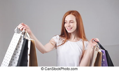 Beautiful smiling redhead girl with a lot of shopping bags....