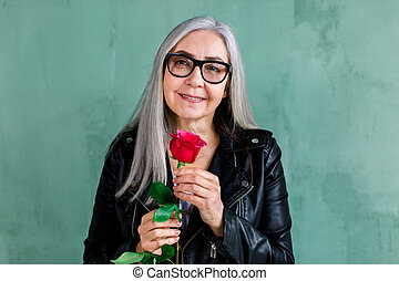 Beautiful smiling senior lady with long straight gray, wearing eyeglasses and stylish black leather jacket, posing on camera, standing on green wall background, holding fresh red rose in hand