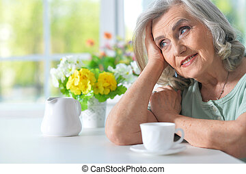 Beautiful smiling senior woman with cup of tea at kitchen