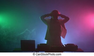 Beautiful, smiling, sexy dj girl in white jacket, headphones playing music and dancing, hands on her head, smoke, silhouette, slow motion