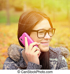 Beautiful smiling student girl talking on cell phone