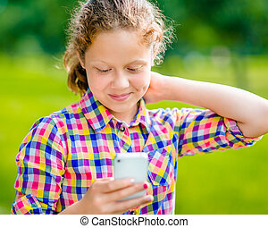 Beautiful smiling teenage girl in casual clothes with smartphone in her hand, looking at screen, reading a message, using Facebook in sunny day in summer park