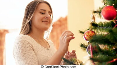 Beautiful smiling woman adorning Christmas tree with baubles...