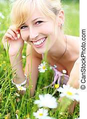 Beautiful smiling woman amongst spring flowers