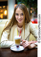Beautiful smiling woman drinking coffee coctail in cafe