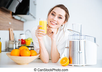 Beautiful smiling woman drinking fresh orange juice -...