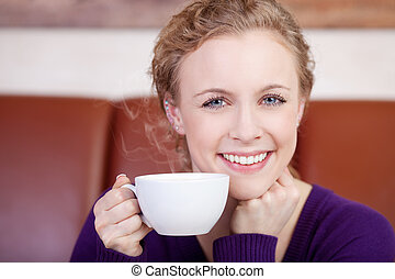 beautiful smiling woman enjoying cup of coffee