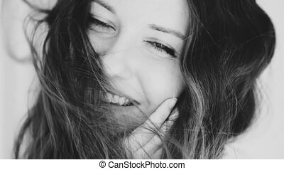 Beautiful smiling woman face with natural makeup, shiny skin and healthy toothy smile, closeup portrait and windswept brown hair. High quality FullHD footage