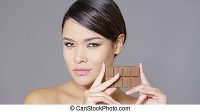 Beautiful smiling woman holding chocolate
