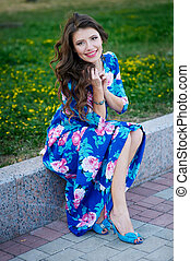 beautiful smiling woman in a blue dress sitting on the kerb in the Park