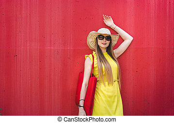 Beautiful smiling woman in a yellow dress in front of a red wall