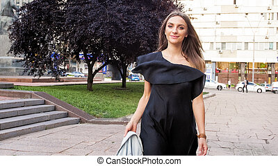 Beautiful smiling woman in black dress walking on city street