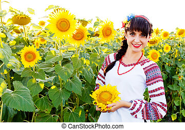 Beautiful smiling woman in embrodery holding a sunflower on a field