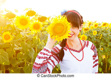 Beautiful smiling woman in embrodery holding sunflower on a field
