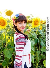 Beautiful smiling woman in  embrodery on a sunflower field