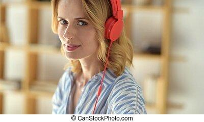 Beautiful smiling woman in headphones posing for camera