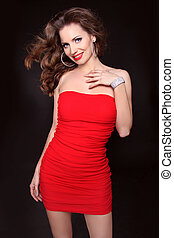 Beautiful smiling woman in red dress posing isolated on black background, studio shot