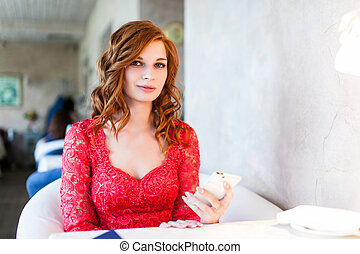woman in red dress sitting in a cafe with her mobile phone