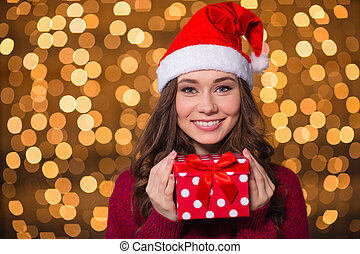 Beautiful smiling woman in santa claus hat with small gift