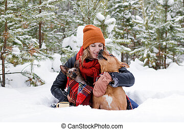 Beautiful smiling woman is sitting on a snow with her two dogs wrapped in red checkered plaid in winter coniferous forest.