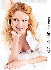 Beautiful smiling woman laying on bed