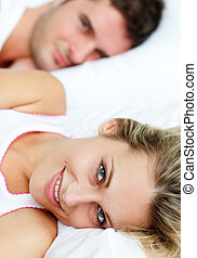 Beautiful smiling woman lying in bed with her boyfriend