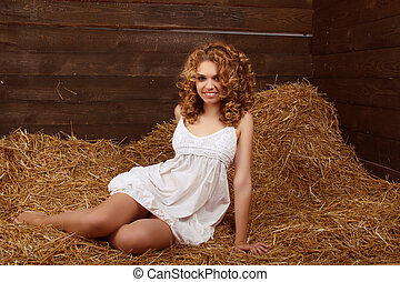 Beautiful smiling woman portrait with long curly hairs on haystack, harvest background
