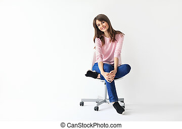 Beautiful smiling woman sitting on chair with copy space