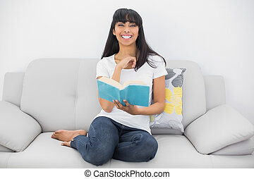 Beautiful smiling woman sitting on couch holding a book