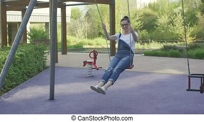 Beautiful smiling woman swinging on playground