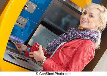 Beautiful smiling woman using an bank ATM
