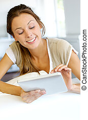 Beautiful smiling woman using digital tablet at home