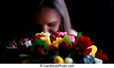 Beautiful smiling woman with a large bouquet of flowers in her arms smelling a fragrant colorful roses on black background.