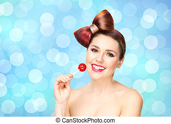Beautiful smiling woman with a lollipop on bubble background.