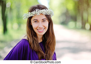 beautiful smiling woman with a wreath on his head in the summer park