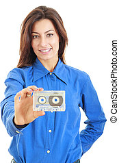 Beautiful smiling woman with audio cassette in her hand