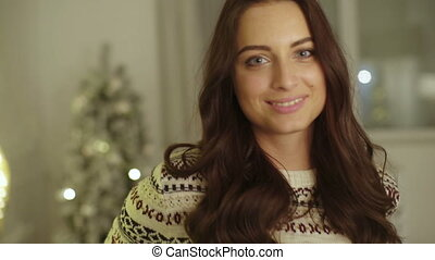 Beautiful smiling woman with brown hair posing on camera on Christmas time.