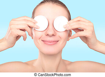 Beautiful smiling woman with cotton pads