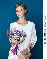 Beautiful smiling woman with gift and flowers. Young happy female model in white dress on blue background