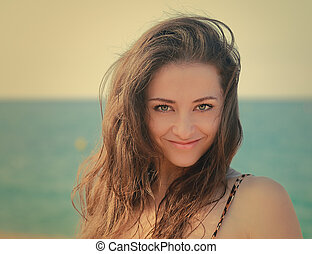 Beautiful smiling woman with long hair looking on beach background