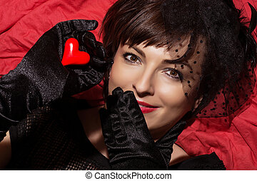 Beautiful smiling woman with red heart in hand
