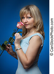 beautiful smiling woman with rose in a studio